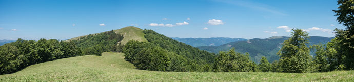 Panoramic view of spring mountains under blue sky Royalty Free Stock Image