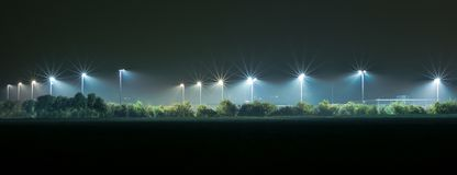 Athletic field illuminated by bright lights in the dark stock image