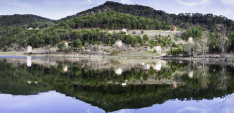 Panoramic view of stone windmills and forest reflection on water. Cubuk lake near Goynuk province in Bolu Turkey Stock Images