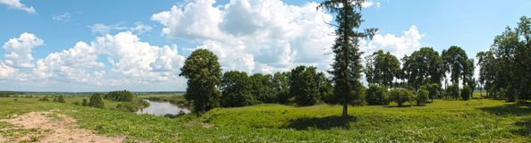 Panoramic view of the summer landscape with a river, blue sky and shores, covered with green grass and tall deciduous trees royalty free stock image