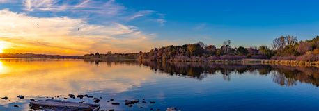 Panoramic view of sunset with beautiful skyline over lake Zorinsky Omaha Nebraska. There is reflection of the sun, skyline and the surrounding forest with fall royalty free stock photography