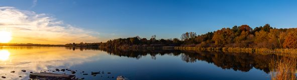 Panoramic view of sunset with fall colors with reflections in the lake. Panoramic view of sunset with fall colors at the lake edge with reflections in the water stock photos