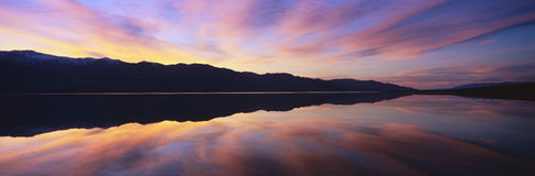 Panoramic view at sunset of flooded salt flats and Panamint Range Mountains in Death Valley National Park, California Stock Image