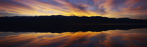 Panoramic view at sunset of flooded salt flats and Panamint Range Mountains in Death Valley National Park, California Stock Photos