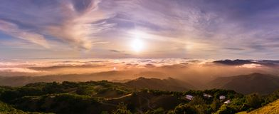 Panoramic view of a sunset over a sea of clouds covering south San Francisco bay area; beautiful rolling hills in the foreground;. View from Mt Hamilton, San stock photography