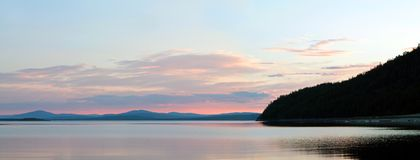 Panoramic view of the sunset in a sea bay with the silhouettes of mountains on the horizon. Coast of the White Sea Kola Peninsula, Russia Stock Photo