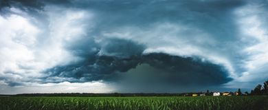 Panoramic view of a terrifying dark thunderstorm approaching stock photography