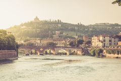 View of the Ponte Pietra bridge on the Adige river illuminated by the sunset in Verona stock photo