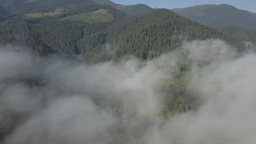 Flying over fog and clouds in Carpathians mountains near by Dzembronya village, Ukraine. Panoramic view to Carpathians mountains with fog and clouds near by stock video footage