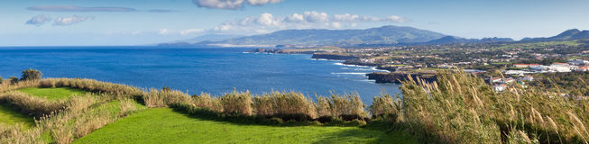 Panoramic view to the field, town and mountains. Panoramic view to the green field, town and mountains at the Atlantic ocean coast, San Miguel, Azores, Portugal Stock Image