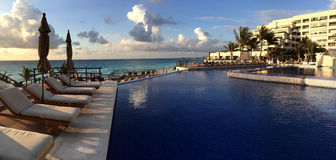 Panoramic view to the swimming pool in the resort at sunrise tim Royalty Free Stock Images