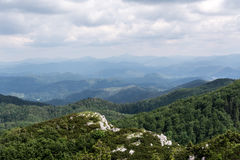 Panoramic view from the top of mountain to many mountain peaks around Royalty Free Stock Photo