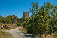 Panoramic view of tower on top of hill and path with tree near Châteaudouble. Royalty Free Stock Images