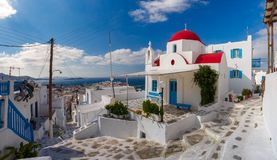 Typical Greek white Church on island Mykonos, Greece. Panoramic view with traditional church with red dome and whitewashed facade, typical Greek church building stock image