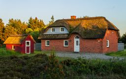 Panoramic view of a traditionally brick built house, thatched roof and small cottage with many green in the foreground. Beautiful royalty free stock images