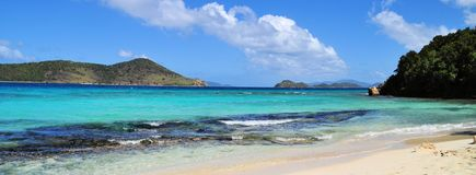 A panoramic view of a tropical carribean beach. A panoramic view of a tropical beach in the carribean with islands, blue skys and clouds in the background Royalty Free Stock Photos