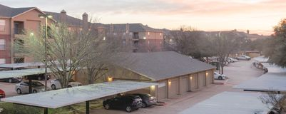 Panoramic view typical apartment complex with detached garage, covered parking lots at sunrise. Panorama view typical aerial of apartment complex with detached royalty free stock photo