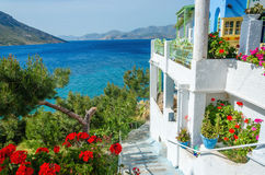 Panoramic view on typical Greek studio with flowers and white te. Racce having clear view on sea landspace with islands, Greece Royalty Free Stock Image