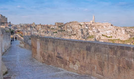 Panoramic view of typical stones and church of Matera shot from typical old street, under blu sky Royalty Free Stock Photos
