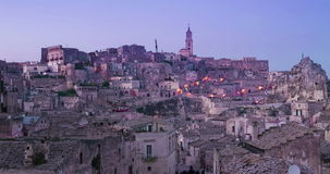 Panoramic view of typical stones and church of Matera under sunset sky time lapse. 4K and 1080p stock footage