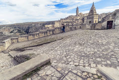 Panoramic view of typical stones Sassi di Matera and church of Matera with a couple in love under blue sky Stock Image
