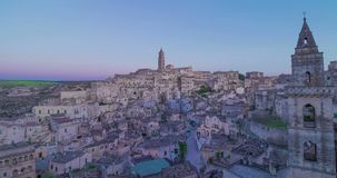 Panoramic view of typical stones Sassi di Matera and church of Matera under blue night sky, time lapse effect, movement. Transition of the sky from day to night stock footage