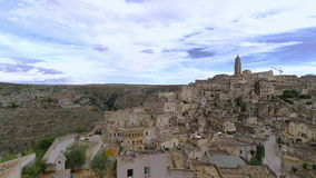 Panoramic view of typical stones (Sassi di Matera) and church of Matera under blue sky. Artistic style. Matera in Italy UNESCO European Capital of Culture 2019 stock footage