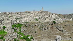 Panoramic view of typical stones Sassi di Matera and church of Matera under blue sky. Basilicata, Italy. Dolly camera movement stock footage