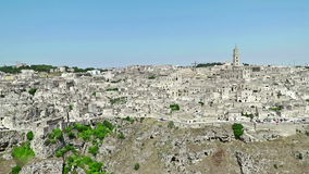 Panoramic view of typical stones Sassi di Matera and church of Matera under blue sky. Basilicata, Italy, dolly camera. Movement stock footage