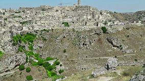 Panoramic view of typical stones Sassi di Matera and church of Matera under blue sky. Basilicata, Italy, tilt camera. Movement stock video footage