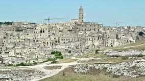 Panoramic view of typical stones Sassi di Matera and church of Matera under blue sky. Basilicata, Italy, zoom out camera. Movement stock footage