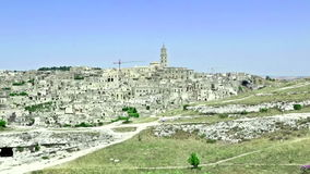 Panoramic view of typical stones Sassi di Matera and church of Matera under blue sky. Basilicata, Italy. Zoom out camera movement stock video footage
