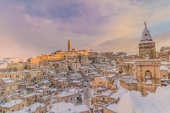 Panoramic view of typical stones Sassi di Matera and church of Matera 2019 under blue sky with clouds and snow on the house, stock photography