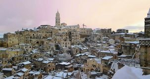 Panoramic view of typical stones Sassi di Matera and church of Matera 2019 with snow on the house, concept of travel and. Christmas holiday on snowflakes at stock footage