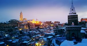 Panoramic view of typical stones Sassi di Matera and church of Matera 2019 with snow on the house, concept of travel and. Christmas holiday on snowflakes at stock video footage