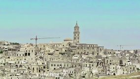Panoramic view of typical stones Sassi di Matera and church of Matera under blue sky. Basilicata, Italy, zoom out camera. Movement stock video footage