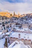 Panoramic view of typical stones Sassi di Matera and church of Matera 2019 under blue sky with clouds and snow on the house, royalty free stock photography