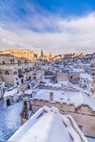 Panoramic view of typical stones Sassi di Matera and church of Matera 2019 under blue sky with clouds and snow on the house, royalty free stock image