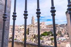 Panoramic view of typical stones (Sassi di Matera) and church of Matera view through gate under blue sky Stock Photo