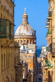 Malta, Streets of Valletta. The church of Our Lady of Mount Carmel and one of the main streets of the Maltese capital, Valletta, Malta Stock Image