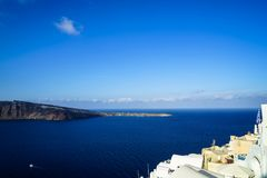 Panoramic view of vast blue Aegean sea, sailing ships and natural caldera mountain from Oia village with white buildings. Along island foreground and blue sky Royalty Free Stock Image