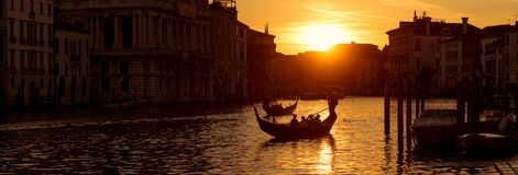 Panoramic view of Venice at sunset, Italy. Horizontal banner of Venice for website header. Gondolas with tourists sail along the Grand Canal in Venice Royalty Free Stock Photo