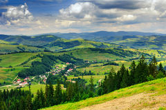 Panoramic view on village in a hilly valley. Panoramic view from the mountains to the village in a hilly valley Stock Photos