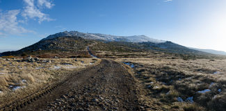 Panoramic view of Vitosha mountain, Bulgaria. Road with tyre tracks and snow covered Cherni Vruh peak in background, Vitosha national park, Bulgaria Stock Photography