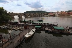 Panoramic view of Vltava river with Charles Bridge and many historical buildings. Small pier with different boats for tourist trip. S. Cloudy summer day royalty free stock photography