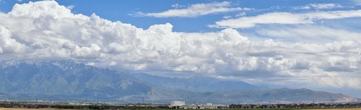 Panoramic view of Wasatch Front Rocky Mountains, Great Salt Lake Valley in early spring with melting snow and Cloudscape. Utah. America Royalty Free Stock Images