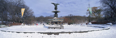 Panoramic view of water fountain covered with fresh winter snow in Central Park, Manhattan, New York City Stock Photo