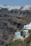 panoramic view of white residences with a pool built on a cliff in Santorini and the town behind royalty free stock images