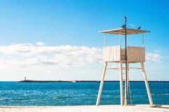 White wooden lifeguard tower or station. Panoramic view of white wooden lifeguard tower or station at blue sea and sky background stock image