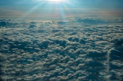 Panoramic view from the window of the plane flying above the sun-drenched clouds stock image
